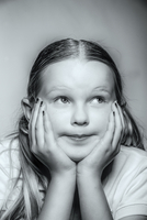 Close up of pensive Caucasian girl resting chin in hands