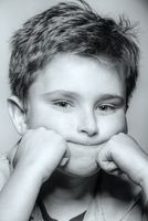 Close up of Caucasian boy resting chin in hands