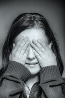 Close up of Caucasian teenage girl covering her eyes