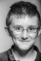 Close up of smiling Caucasian boy with eyeglasses askew