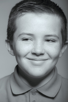 Close up of smiling Caucasian boy looking away