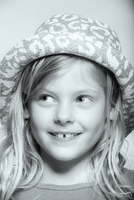 Close up of smiling Caucasian girl wearing hat looking away