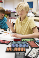 Student using pastels at desk in classroom