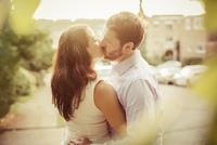 Caucasian couple kissing on sidewalk