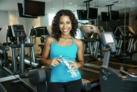 Woman smiling near exercise machines in gymnasium