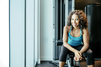 Woman sitting on exercise machine in gymnasium