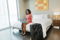 Woman using laptop on bed in hotel room