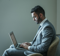Businessman using laptop in armchair