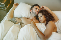 Sleeping couple hugging in bed