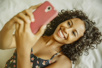 Woman taking selfie with cell phone on bed
