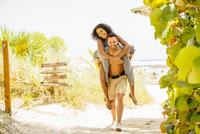 Man carrying girlfriend piggyback on beach