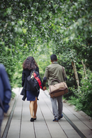 Couple walking on wooden walkway in park