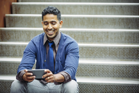 Indian businessman using cell phone on steps