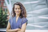 Mixed race businesswoman standing with arms crossed outdoors