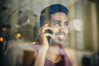Indian man talking on cell phone in cafe