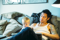 Father and son reading on sofa in living room