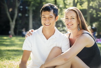 Smiling couple sitting on grass in park