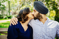 Indian couple kissing on bench in urban park