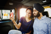 Indian couple taking selfie with cell phone in taxi