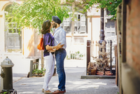 Indian couple kissing on city sidewalk