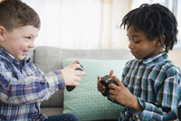Boys playing video games on sofa