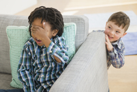 Close up of boys playing hide and seek in living room