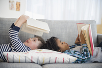 Boys reading on living room sofa