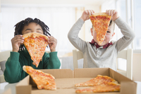 Boys eating pizza from cardboard box