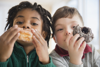 Close up of boys eating donuts