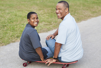 African American father and son sitting on skateboard on path