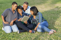 African American family using digital tablet on grass
