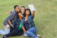 African American family taking selfie with digital tablet on grass