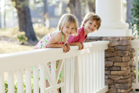 Caucasian brother and sister leaning over porch