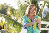 Hispanic woman using cell phone on patio
