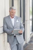 Caucasian businessman using digital tablet in city