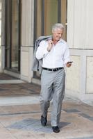 Caucasian businessman using cell phone on city sidewalk
