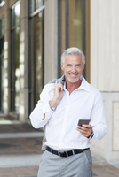 Caucasian businessman using cell phone in city