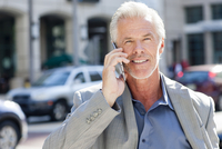 Caucasian businessman talking on cell phone in city