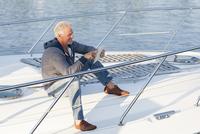 Caucasian man using digital tablet on sailboat deck