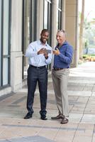 Businessmen using cell phone on city sidewalk