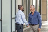 Businessmen shaking hands in city