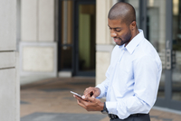 Black businessman using cell phone outside office
