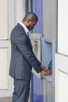 Black businessman using ATM in city