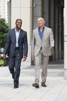 Businessmen talking on city sidewalk