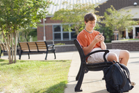 Caucasian teenage boy using cell phone on bench