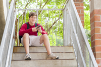 Caucasian teenage boy using cell phone on steps
