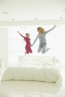 Caucasian mother and daughter jumping on bed