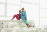 Caucasian mother and daughter sitting on bed