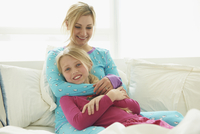 Caucasian mother and daughter playing on bed