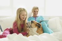 Caucasian mother and daughter relaxing with dog on bed